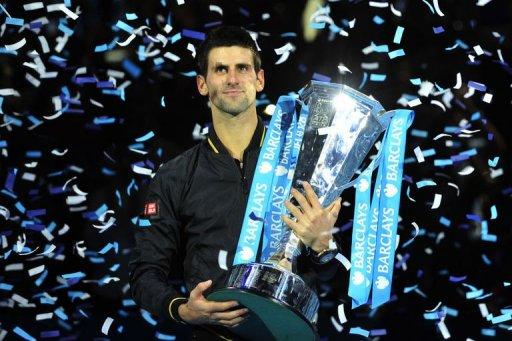 Novak Djokovic poses with the winners' trophy