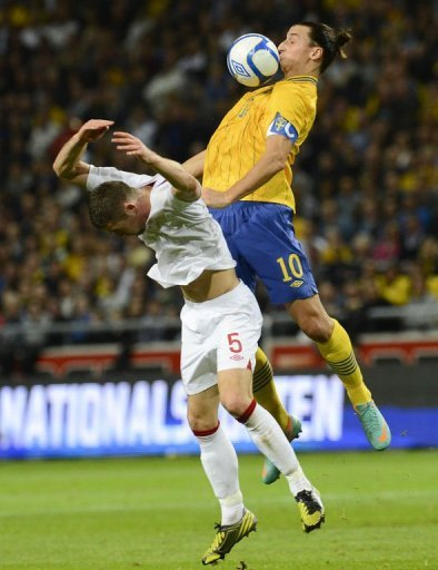 Sweden's Zlatan Ibrahimovic (L) vies for the ball with England's Gary Cahill
