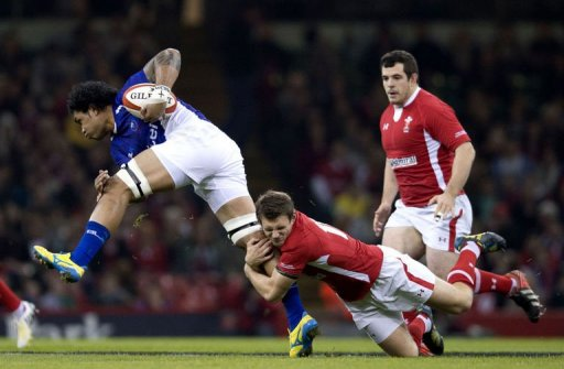 Wales' left wing George North (C) tackles Samoa's left wing David Lemi (L)