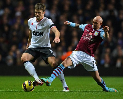 Aston Villa's Stephen Ireland (R) fights for the ball with Manchester United's Michael Carrick