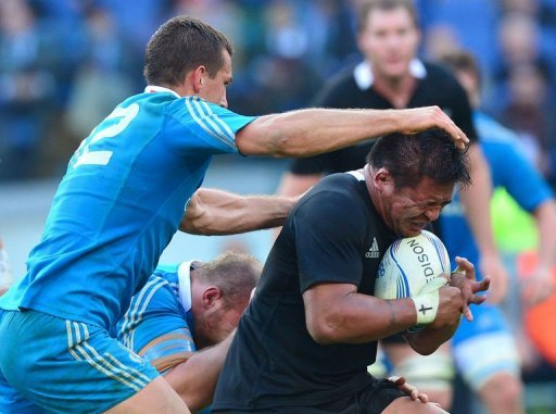 All Blacks hooker Keven Mealamu (R) is tackled by Italy's centre Alberto Sgarbi