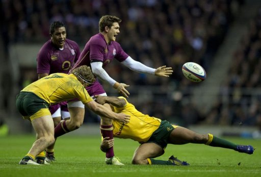 England's full back Alex Goode (C) is tackled by Australia's flanker Michael Hooper (L) and fly half Kurtley Beale (R)