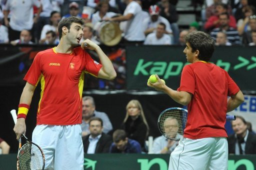 Spanish tennis player Marcel Granollers (L) talks with his teammate Marc Lopez