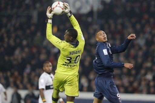 Rennes' goalkeeper Cheik Ndiaye (L) grabs the ball in front of Paris Saint-Germain's forward Guillaume Hoarau