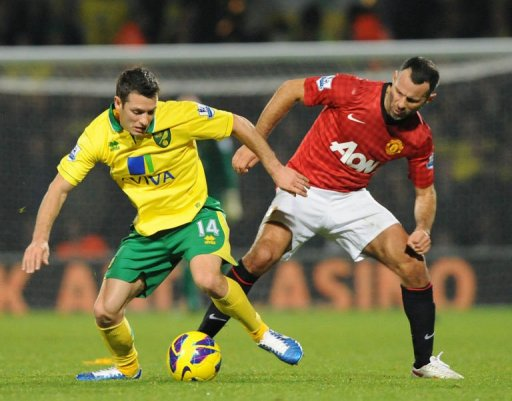 Manchester United's midfielder Ryan Giggs (R) clashes with Norwich City's midfielder Wes Hoolahan