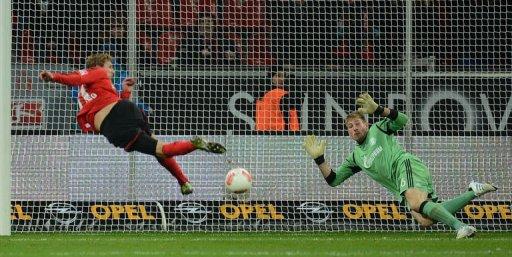 Leverkusen's striker Stefan Kiessling (L) scores past Schalke's goalkeeper Lars Unnerstall