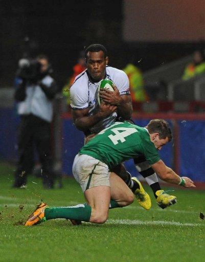 Ireland wing Craig Gilroy tackles Fiji wing Simeli Koniferedi (L)