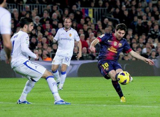 Barcelona's forward Lionel Messi (R) scores