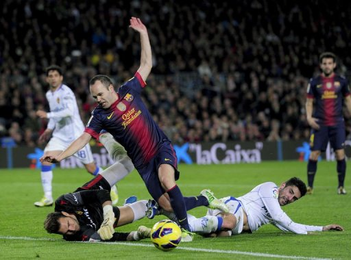 Barcelona's Andres Iniesta (C) collides with Zaragoza's Alvaro Gonzalez (R) and goalkeeper Roberto Jimenez Gago