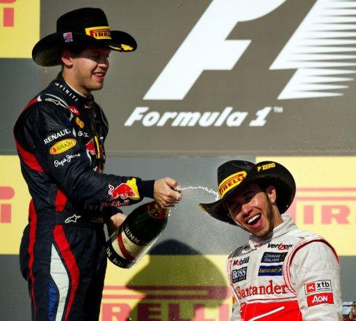 Sebastian Vettel (L) sprays champagne on Lewis Hamilton