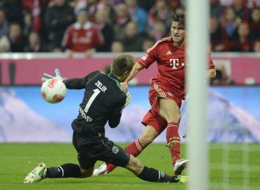 Bayern Munich's striker Mario Gomez (R) scores the fifth goal for Munich against Hanover's goalkeeper Ron-Robert Zieler