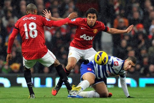 Manchester United's Brazilian defender Rafael (C) and English forward Ashley Young (L) challenge QPR's Adel Taarabt