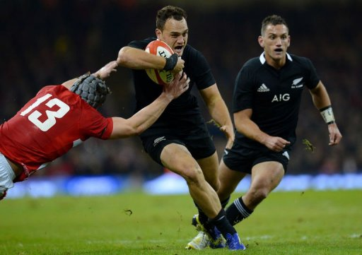 New Zealand's Israel Dagg (C) slips past Wales' Jonathan Davies (L) during the Autumn International rugby union match