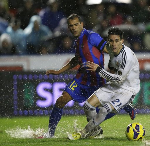 Levante's Juanfran Garcia (L) fights for the ball with Real Madrid's Jose Maria Callejon