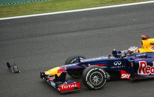 Sebastian Vettel passes by debris from a car at the S of Senna turn