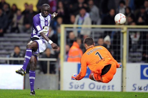 Toulouse's Cheick Mbengue (L) vies with Lyon's goalkeeper Remy Vercoutre