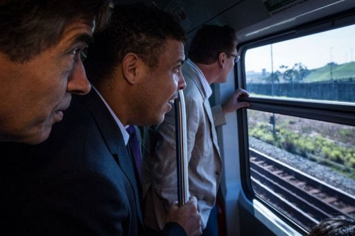 Ronaldo (C) and FIFA Secretary General Jerome Valcke (R) ride a train to the construction site of the Itaquerao stadium