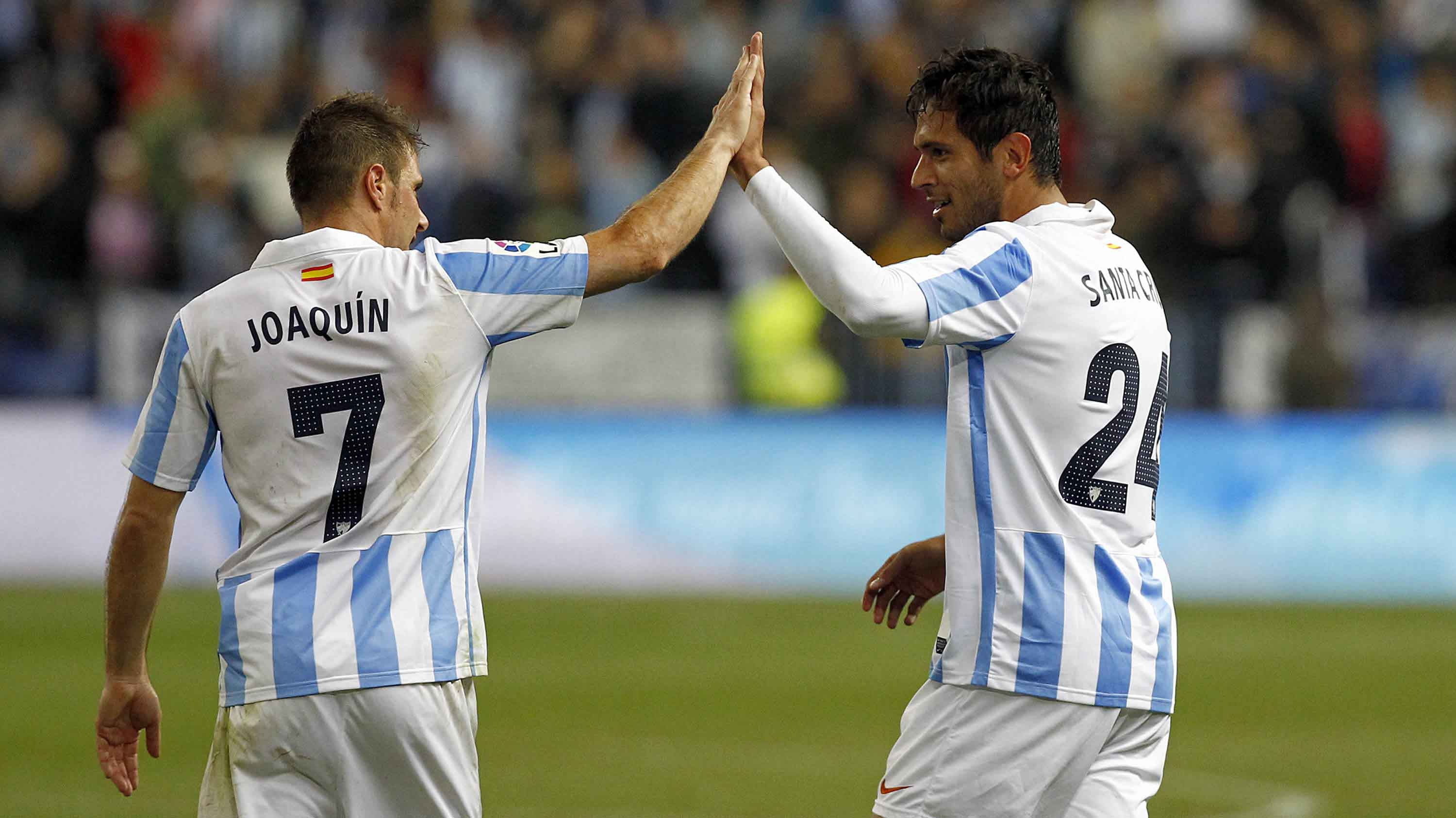 Joaquin and Santa Cruz combined twice for two goals that gave Malaga a 3 - 1 advantage