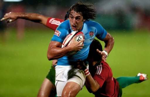 England's Dan Bibby (C) escapes a tackle by two Portuguese players