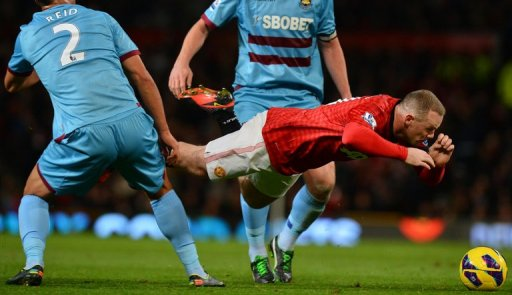 Manchester United's Wayne Rooney (R) falls as he fights for the ball with West Ham United's Winston Reid (L)