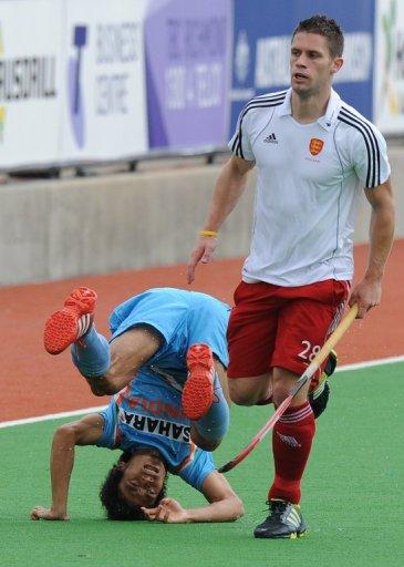 Mark Gleghorne of England runs past Kothajit Singh of India