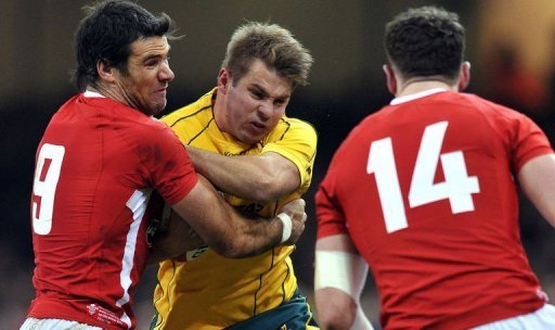 Australia's wing Drew Mitchell (centre) is tackled by Wales's scrum half Mike Phillips (left) and wing Alex Cuthbert