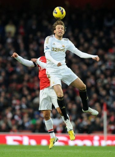 Swansea City's midfielder Miguel Michu (R) beats Arsenal's defender Thomas Vermaelen (L) for a high ball