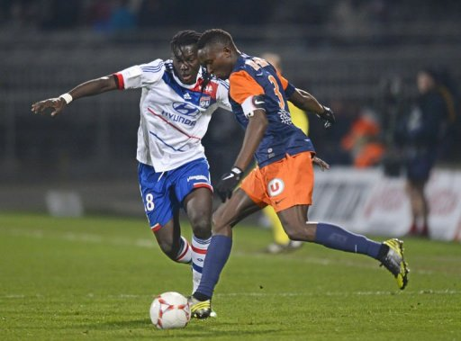 Lyon's forward Bafetimbi Gomis (L) fights for the ball with Montpellier's defender Mapou Yanga-Mbiwa