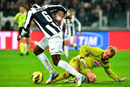Juventus' midfielder Paul Pogba (L) fights for the ball with Torino's goalkeeper Jean Francois Gillet