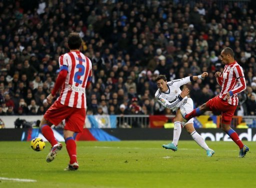 Real Madrid midfielder Mesut Ozil scores the second goal during their match against Atletico Madrid