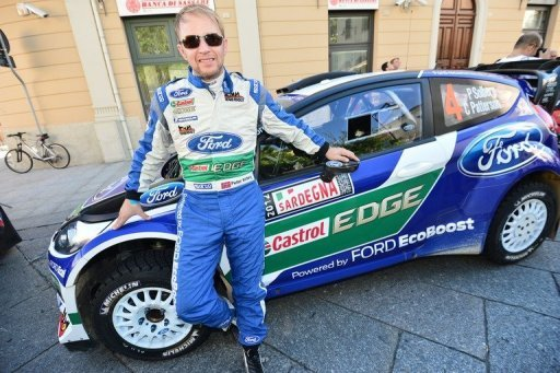 Norvegian driver Petter Solberg poses near his Ford Fiesta RS WRC