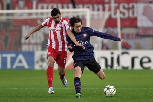 Olympiakos Giannis Maniatis fights for the ball with Arsenal's Tomas Rosicky (R)