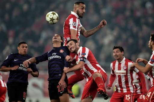 Olympiakos' Kostas Mitroglou (top) and Vassilis Torosidis (C) fight for the ball with Arsenals's Marouane Chamakh