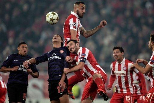 Olympiakos' Kostas Mitroglou (top) and Vassilis Torosidis (C) outmuscle Marouane Chamakh