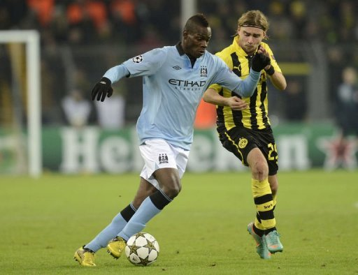 Manchester's striker Mario Balotelli (L) and Dortmund's defender Marcel Schmelzer fight for the bal
