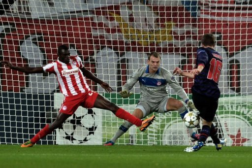 Olympiakos' goalie Roy Carrol eyes the ball after a shot by Arsenal's Aaron Ramsey