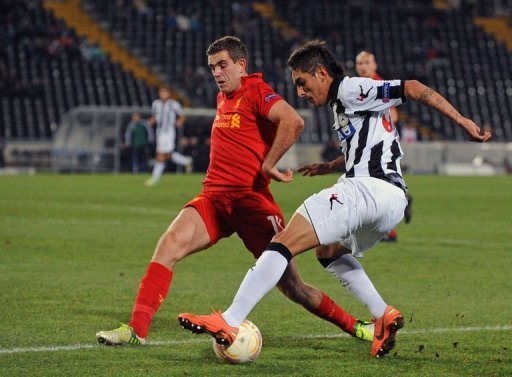 Liverpool's Jordan Henderson (L) fights for the ball with Udinese's Roberto Maximilliano Pereyra