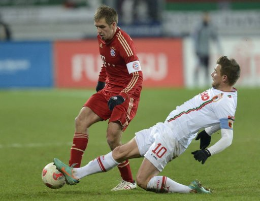 Bayern Munich's defender Philipp Lahm (L) and Augsburg's midfielder Daniel Baier challenge for the ball