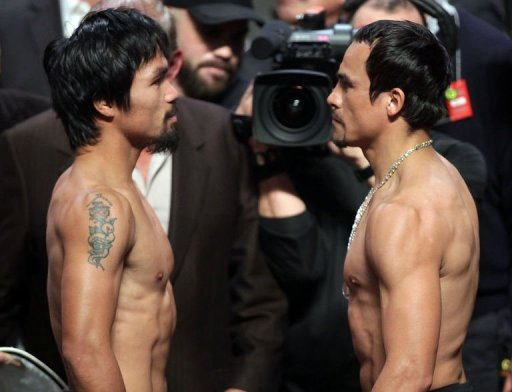 Manny Pacquiao (L) of the Philippines faces Juan Manuel Marquez (R) of Mexico during their weigh-in