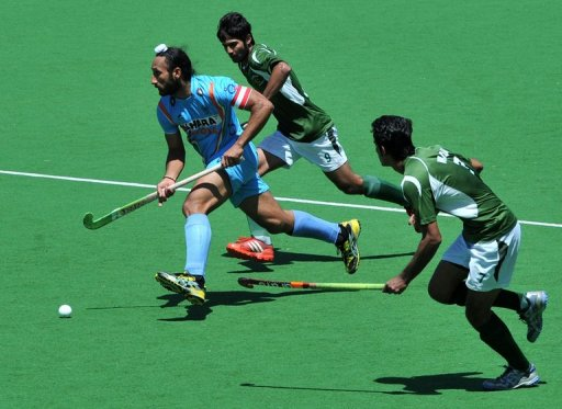 Captain Sadar Singh of India (left) runs through Muhammad Waqas and Haseem Abdul Khan of Pakistan