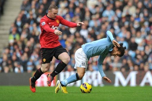 Manchester United's Wayne Rooney (L) vies with Manchester City's David Silva