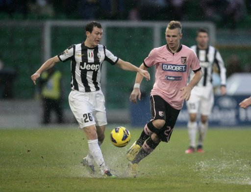 Juventus's Stephan Lichtsteiner (L) is challenged by Palermo's defender Jasmin Kurtic