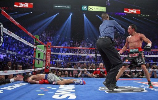 Referee Kenny Bayless (C) holds back Juan Manuel Marquez (R) as Manny Pacquiao (L) lies face down on the mat