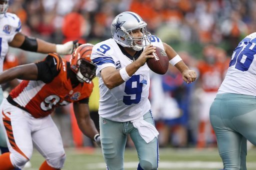 Tony Romo of the Dallas Cowboys looks to pass the ball while under pressure against the Cincinnati Bengals