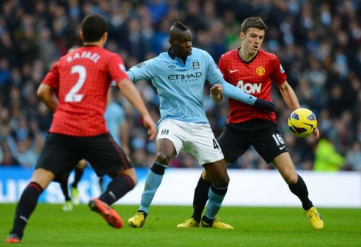 City's Mario Balotelli (C) vies with United's Michael Carrick (R)
