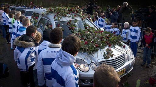 Members of SC Buitenboys lay roses on a hearse carrying the body of linesman Richard Nieuwenhuizen