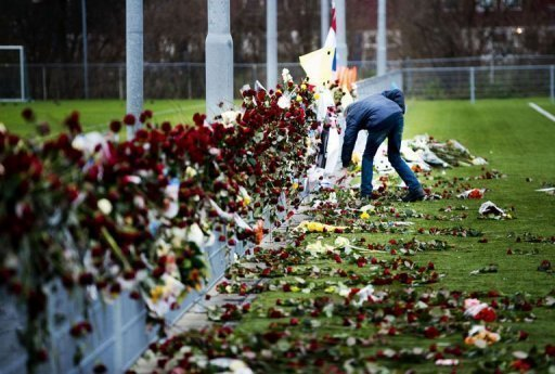 A man looks at the flowers at Richard Nieuwenhuizen's memorial site in Almere, Netherlands