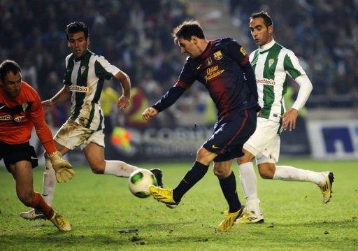 Barcelona's Argentinian forward Lionel Messi (2nd R) vies with Cordoba's goalkeeper Mikel Saizar (L)