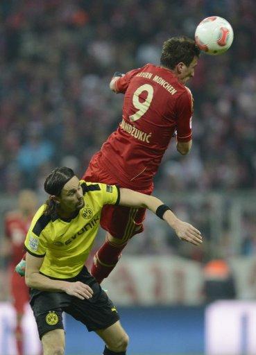 Bayern striker Mario Mandzukic outjumps Dortmund's Neven Subotic during the German Bundesliga match on December 1, 2012
