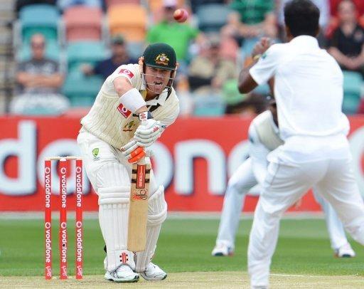 Australian batsman David Warner hits the ball back to Sri Lankan bowler Nuwan Kulasekara in Hobart on December 14, 2012